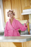 Homemaker. Woman wearing a pink robe and rollers in her kitchen stock image