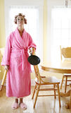 Homemaker. Woman wearing a pink robe and rollers in her dining room, holding a frying pan royalty free stock photo