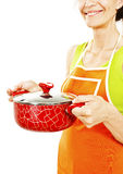 Homemaker in an apron holding pan with ready meal, soup Stock Images
