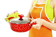 Homemaker in an apron holding pan with ready meal, soup Royalty Free Stock Images