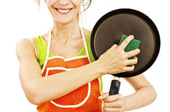 Homemaker in an apron holding a pan and sponge washer Royalty Free Stock Image