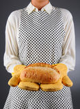 Homemaker Holding Fresh Loaf of Bread. Closeup of a homemaker in an apron and oven mitts holding a fresh baked loaf of bread. Horizontal format over a light to stock image
