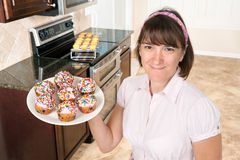 Homemaker holding plate of cupcakes Royalty Free Stock Photos