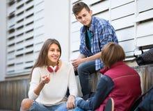 Homens adolescentes e fala da menina Foto de Stock Royalty Free