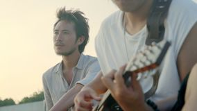 Homens adultos asiáticos novos que cantam jogando a guitarra video estoque