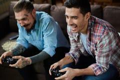 Homens adultos modernos na batalha do jogo de vídeo Imagem de Stock