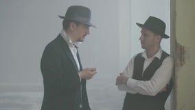 Homens adultos seguros do retrato dois na posição do chapéu do fedora no lugar e na fala durty quebrados Abandonado dilapidado video estoque