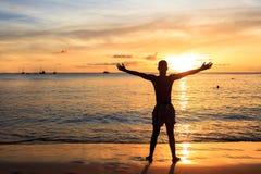 Homens africanos que aumentam os braços acima no por do sol na praia de Tarrafal em San imagem de stock
