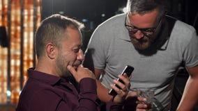 Homens alegres que brindam e que sorriem à câmera, descansando na barra vídeos de arquivo