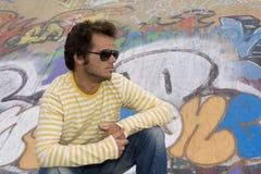 Homens ao lado de uma parede dos grafittis imagens de stock
