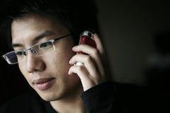 Homens asiáticos novos na chamada imagem de stock