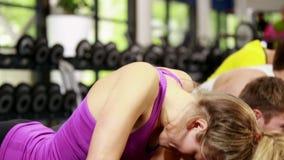 Homens atléticos e mulheres que fazem flexões de braço video estoque