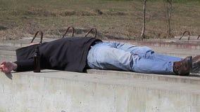 Homens bêbados que dormem perto da garrafa do álcool vídeos de arquivo