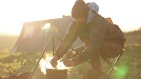 Homens caucasianos que cozinham o alimento no boowler na fogueira no acampamento filme