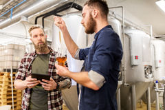 Homens com cerveja do ofício dos testes da pipeta na cervejaria Fotografia de Stock