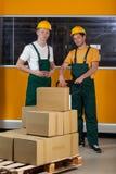 Homens com o caminhão de pálete da forquilha completamente das caixas Fotos de Stock Royalty Free