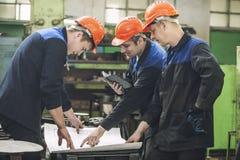 Homens com os desenhos que trabalham em uma fábrica velha para instalar o equipamento imagens de stock