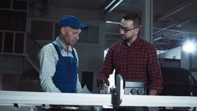 Homens com papéis na obra de carpintaria Fotografia de Stock