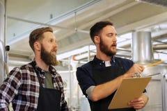 Homens com a prancheta na cervejaria ou na planta da cerveja filme