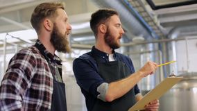 Homens com a prancheta na cervejaria ou na planta da cerveja video estoque