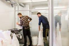 Homens com sacos do malte e moinho na cervejaria da cerveja do ofício imagem de stock