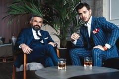 Homens com um grande estilo Dois homens consideráveis novos nos ternos que olham a câmera ao descansar dentro fotografia de stock royalty free