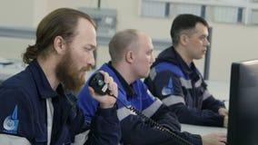 Homens concentrados da vista lateral no uniforme no dever em monitores video estoque