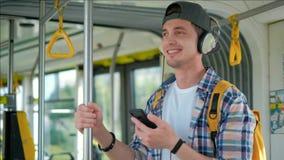 Homens consideráveis novos que apreciam a viagem no transporte público, estando com fones de ouvido ao mover-se no bonde moderno filme