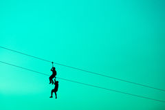 Homens da silhueta que penduram o cabo do cabo Fotos de Stock