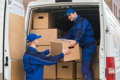 Homens de entrega que descarregam caixas do caminhão Fotografia de Stock