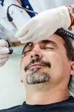 Homens de limpeza da cara do procedimento do esteticista imagem de stock royalty free