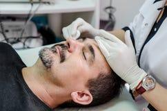 Homens de limpeza da cara do procedimento do esteticista fotos de stock royalty free
