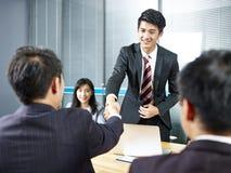 Homens de negócio asiáticos que agitam as mãos antes de encontrar imagem de stock