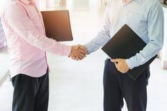Homens de negócio novos que agitam as mãos Imagem de Stock