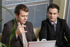Homens de negócio novos que trabalham com latop no escritório Foto de Stock Royalty Free
