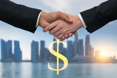 Homens de negócio que agitam as mãos para o negócio com dinheiro do dólar Skyline das construções no fundo Fotografia de Stock Royalty Free