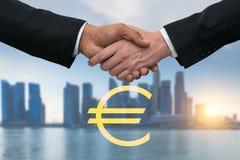 Homens de negócio que agitam as mãos para o negócio com euro- dinheiro Skyline das construções no fundo Fotografia de Stock
