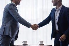 Homens de negócio que agitam as mãos um com o otro após um negócio Imagens de Stock