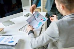 Homens de negócio que discutem o relatório das estatísticas fotos de stock royalty free