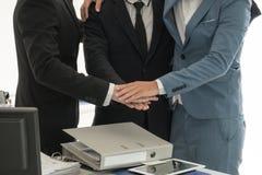 Homens de negócio que juntam-se às mãos junto para ser trabalhos de equipa Fotografia de Stock