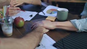 Homens de negócio que põem as mãos sobre a tabela para conectar com a equipe na reunião startup vídeos de arquivo