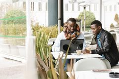 Homens de negócio que usam o móbil e o portátil na cafetaria Fotografia de Stock Royalty Free