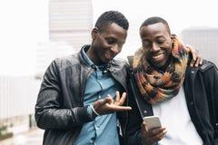 Homens de negócio que usam o móbil na rua Foto de Stock Royalty Free