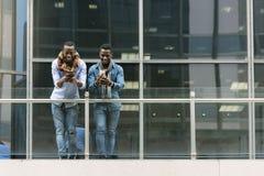 Homens de negócio que usam o móbil na rua Imagens de Stock Royalty Free