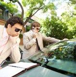 Homens de negócios que encontram-se em torno do carro. Imagens de Stock