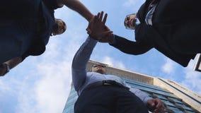 Homens de negócios bem sucedidos que estão e mãos empilhadas junto perto do prédio de escritórios Colegas masculinos que põem seu video estoque
