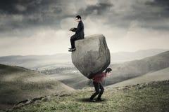 Homens de negócios com portátil e pedra Foto de Stock