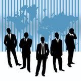 Homens de negócios de encontro a um mapa do mundo Foto de Stock