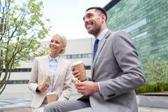 Homens de negócios de sorriso com copos de papel fora Imagem de Stock
