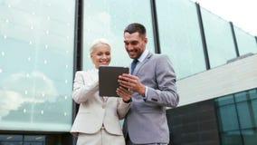 Homens de negócios de sorriso com PC da tabuleta fora Foto de Stock